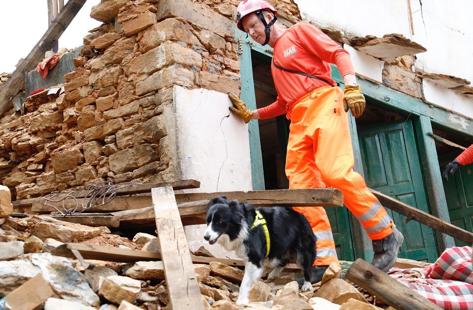 Search and rescue dog and handler walk across rubble